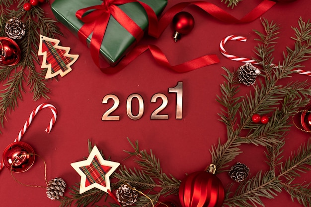 Happy new year 2021. golden digits 2021 with christmas hat are on red background with glitter. holiday party decoration or postcard concept with top view and copy space.