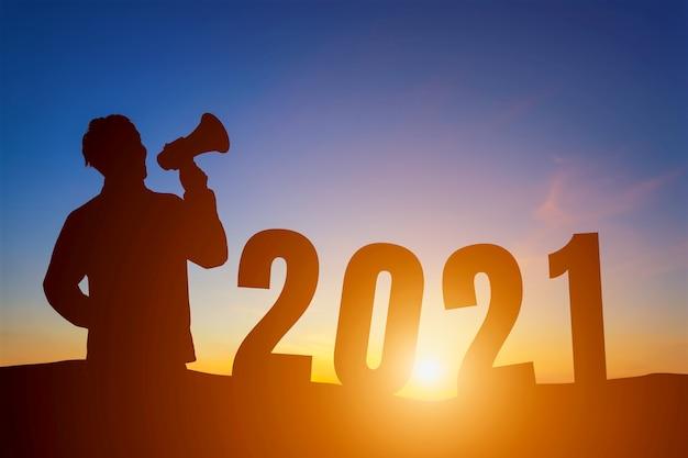 새해 복 많이 받으세요 2021. 실루엣 수평선 배경 위에 확성기 아침 일출 외치고 입고 잘 생긴 젊은 남자