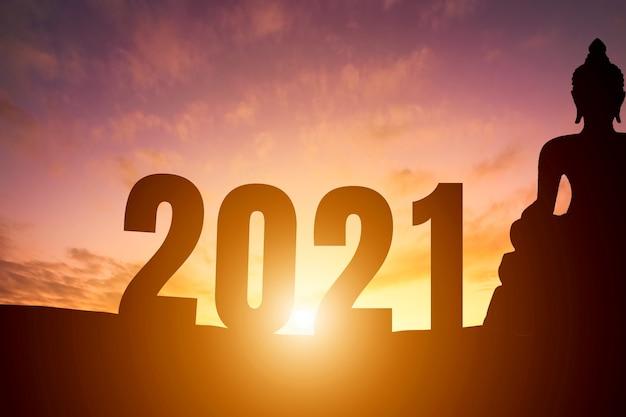 새해 복 많이 받으세요 2021. 수평선 배경 위에 실루엣 부처님 동상 이른 아침 일출