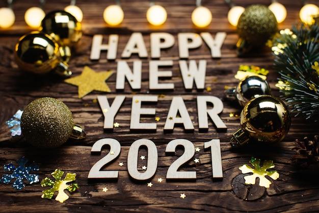 明けましておめでとうございます2021。木製の背景に番号2021からのシンボル