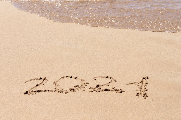 Happy new year 2021 text on the beach. planning vacation.