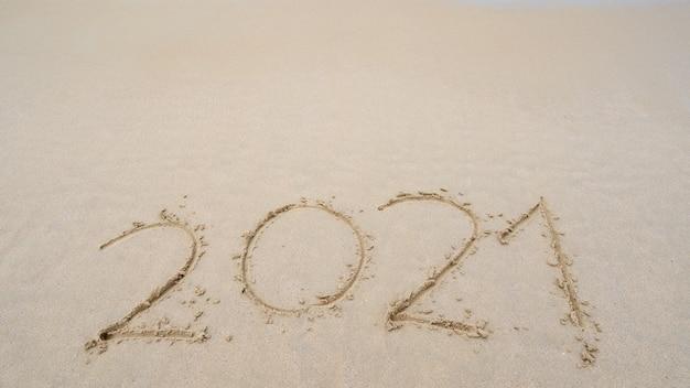 행복 한 새 해 2021 텍스트 해변, 2021 년 메시지 손 아름 다운 해변에 모래에 작성 모래 해변 배경에 공간을 복사합니다. 새해 개념.