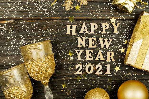 Happy new year 2021 text on wooden surrounded golden christmas toys.