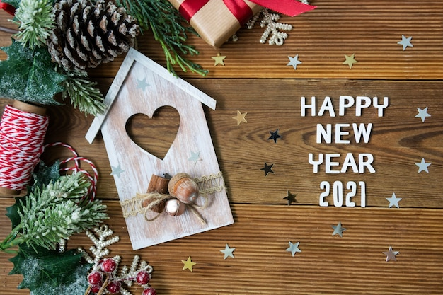 Happy new year 2021 with red gift boxes, fir branches, wooden house and winter decorations.