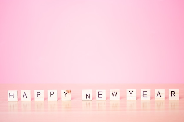 Happy new year 2021 with wood cube on pink background.