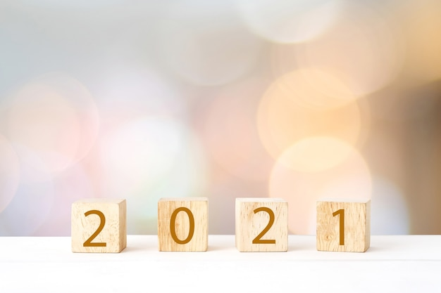 Happy new year 2021 on wood cube block and blur abstract bokeh light