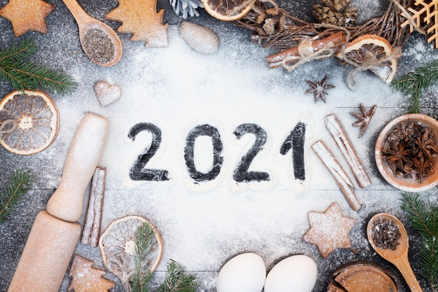 Happy new year 2021 written on flour. christmas tree branches, gingerbread cookies, spices and baking supplies on black wood surface