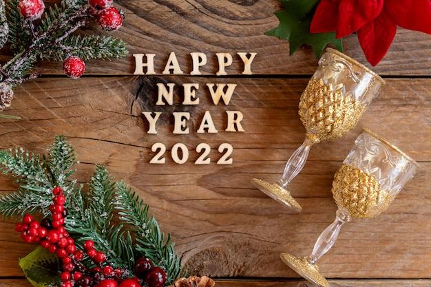 明けましておめでとうございます2022年のお祝い。木製の背景にシャンパングラスとポインセチアの花。フラットレイ。