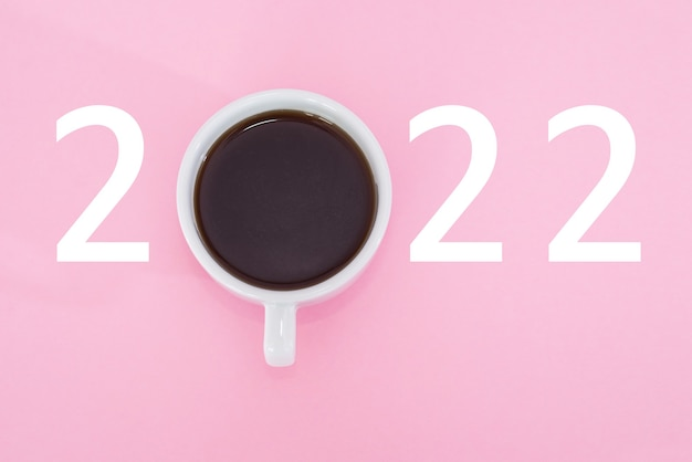 Happy new year 2022. cup of coffee with number 2022 on pink background