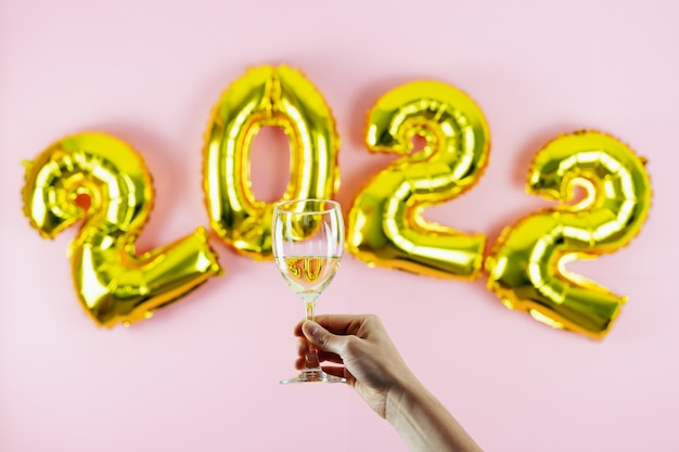 Happy new year 2022. hand toasting on pink background. copy space.