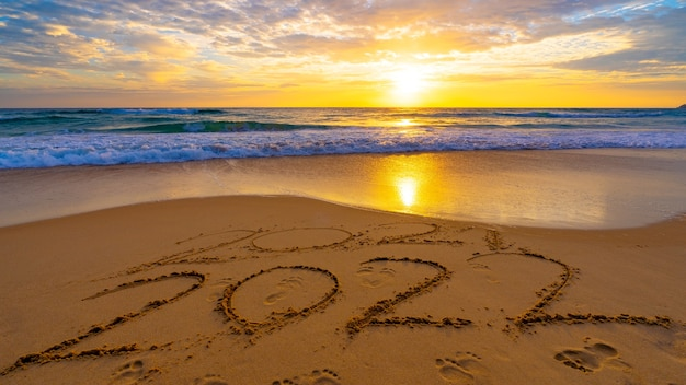 Happy new year 2022, lettering on the beach with waves and sunset sky numbers 2022 year on the seashore, message hand written in the golden sand on beautiful sunset or sunrise golden sky background.