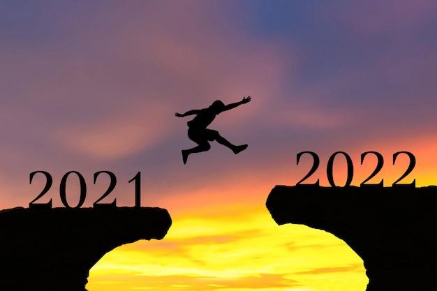 새해 복 많이 받으세요 2022 남자는 실루엣 산과 태양을 뛰어 넘습니다.