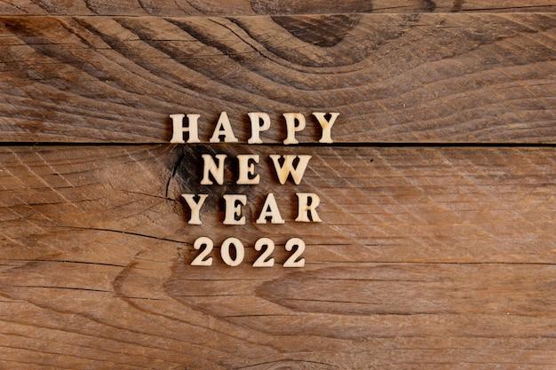 明けましておめでとうございます2022年。木製の背景に木製の文字と数字2022から引用。新年のグリーティングカードの創造的なコンセプト