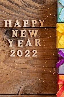 明けましておめでとうございます2022。色とりどりの小さなギフトボックスと木製の背景に木製の文字と数字2022から引用。新年のグリーティングカードの創造的なコンセプト。