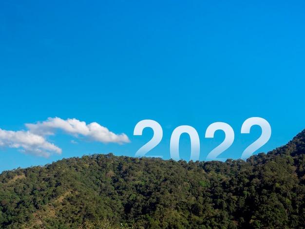 緑豊かな肥沃な山々と青い空に大きな文字、コピースペースのある美しい景色、成功したコンセプトで新年あけましておめでとうございます2022。ようこそ、メリークリスマス、そして2022年の明けましておめでとうございます。