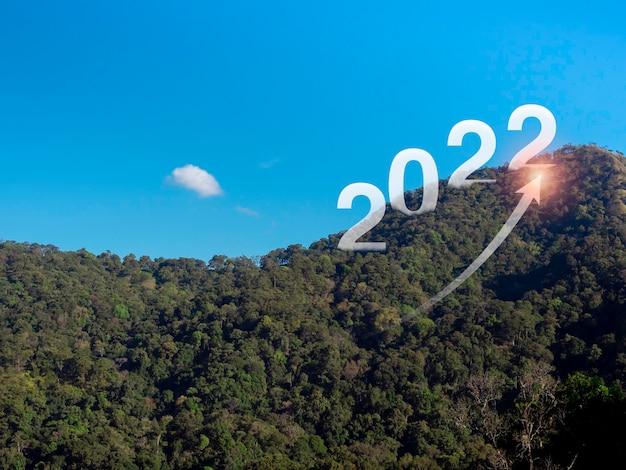 緑豊かな山々に大きな文字と輝く、ビジネス目標の概念を持つ上昇矢印で新年あけましておめでとうございます2022。ようこそ、メリークリスマス、そして2022年の明けましておめでとうございます。