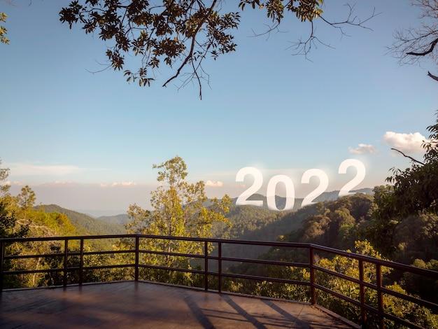 新年あけましておめでとうございます2022年、テラスからの美しい景色を望む山に大きな文字があり、成功したコンセプトです。ようこそ、メリークリスマス、そして2022年の明けましておめでとうございます。