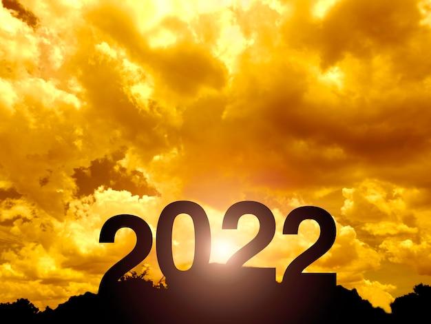 成功のコンセプトのための美しい夕日の光、日光、金色の空と雲と山の上の大きなシルエットの文字で新年あけましておめでとうございます2022。 2022年のメリークリスマスと新年あけましておめでとうございます。