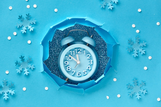 С новым годом! aarm часы в отверстии бумаги, плоский вид сверху лежал на синей бумаге со снегом и снежинками