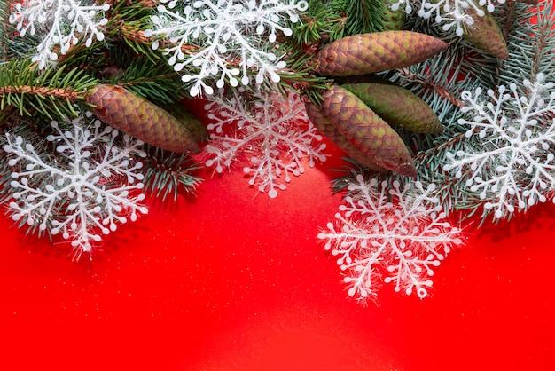 С новым годом и рождеством. красный новогодний фон с елями, конусами и снежинками.