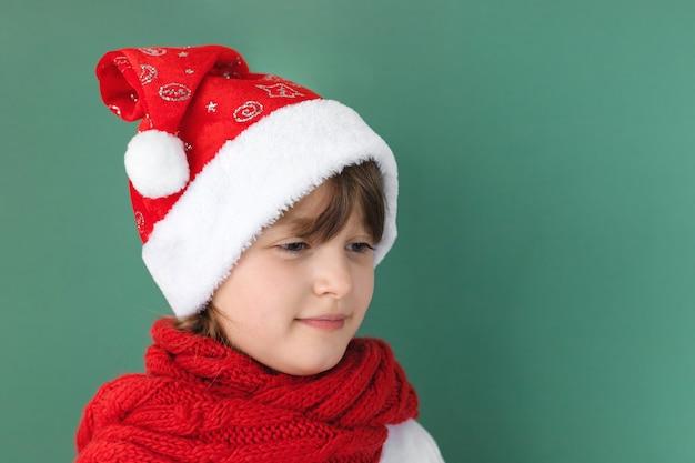 С новым годом и рождеством. милая маленькая кавказская девочка в новогодней шапке и красном шарфе на зеленой стене с местом для текста.