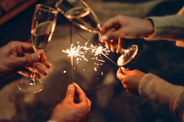 С наступающим новым годом и рождеством! бокалы с шампанским в руке и бенгальские огни.