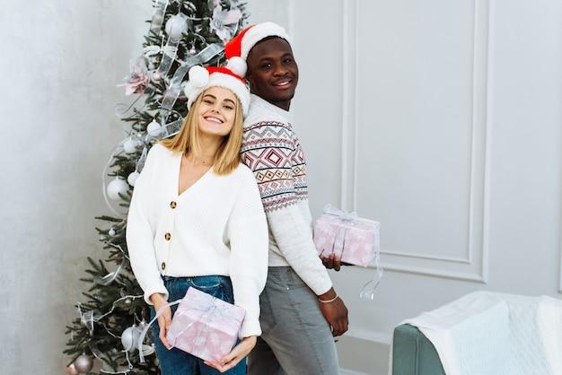 明けましておめでとうとメリークリスマスを一緒に家で。サンタクロースの帽子をかぶった若いアフリカ系アメリカ人の男と白人女性の笑顔は、木と花輪のあるリビングルームのインテリアのカメラを見てください。