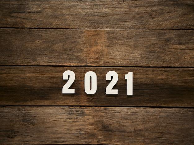 С новым годом фон с числами 2021 года на деревенском темном деревянном фоне. место для текста