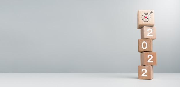 С новым годом баннер. бизнес-цель с номерами года и целевым значком подписывается на деревянных кубических блоках на белом фоне с копией пространства. добро пожаловать, счастливого рождества и счастливого нового года.