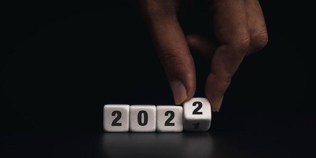 明けましておめでとうございます。 2021年は2022年の概念に変わります。暗い背景、モダンで最小限のスタイルで2021年から2022年までの番号を変更するための白いサイコロブロックを手で弾くクローズアップ。