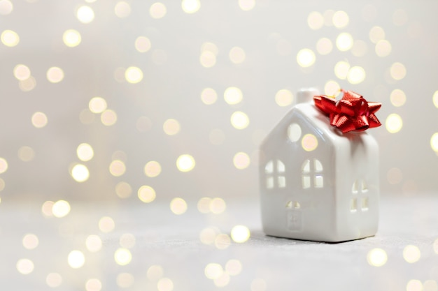 Happy new year banner with small toy model house with red bow