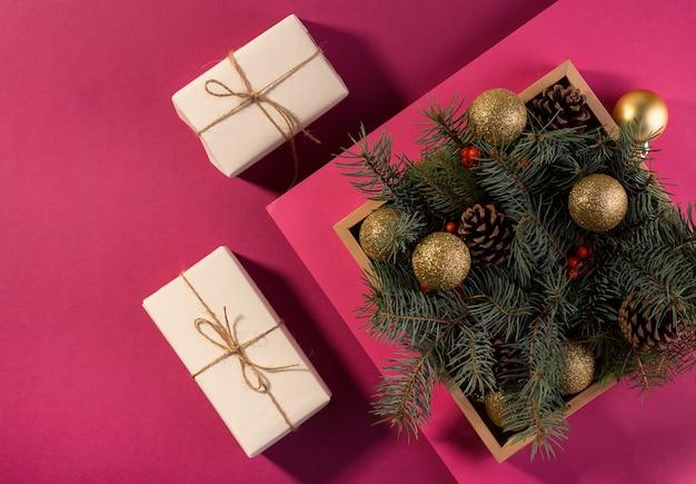 С новым годом карта или баннер с подарочными коробками на фиолетовом фоне, украшенные праздничными еловыми ветками.