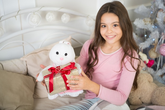 Happy new year. christmas. kid enjoy the holiday. small happy girl at christmas. the morning before xmas. new year holiday. little child girl likes xmas present.