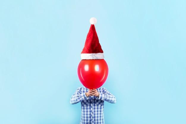 サンタ帽子で赤い風船を持って男と新年あけましておめでとうございますコンセプト