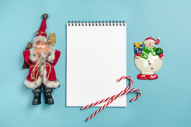 Happy new year flat lay composition with notepad, place for text christmas decor on blue b