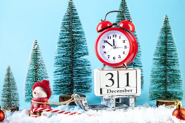 Happy new year greeting card. alarm clock on a wooden sled in the snow
