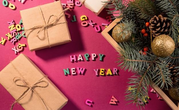 С новым годом поздравительные слова из деревянных букв, подарочные коробки на фиолетовом фоне, украшенные праздничными еловыми ветками.