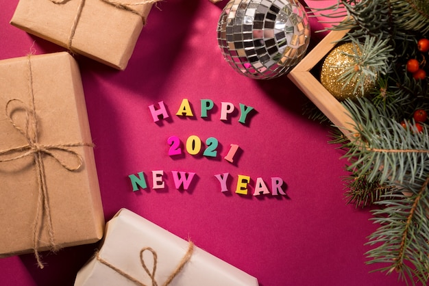 Happy new year greeting words made of wooden letters, gift boxes on a purple background decorated with festive fir tree branches.