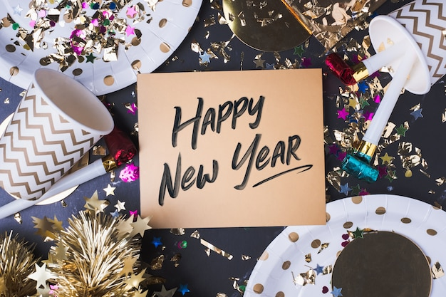 Happy new year handwriting on golden greeting card with party cup