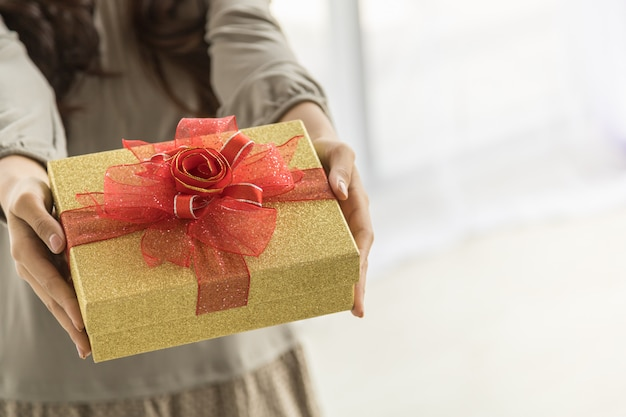 Happy new year and holiday seasonal concept. close up of beautiful gift box holding and present by asian young woman