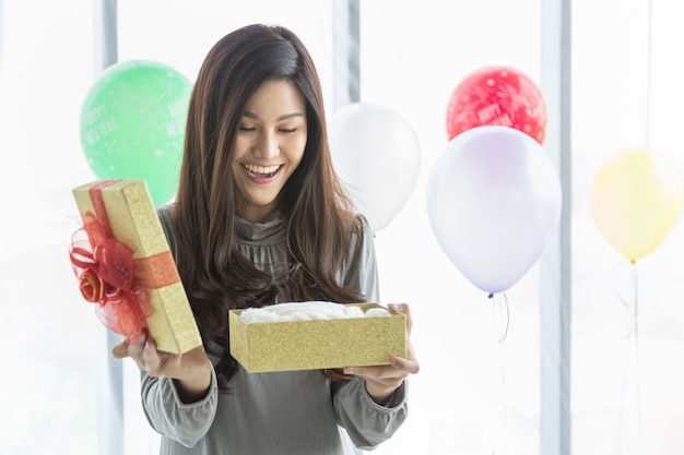 Happy new year and holiday seasonal concept. portrait of beautiful asian young woman smiling and  surprised with gift box with colorful balloon as background.