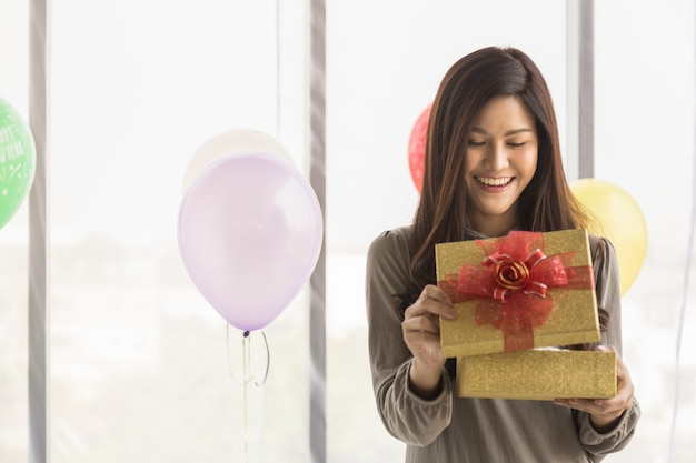 Happy new year and holiday seasonal concept. portrait of beautiful asian young woman smiling and  surprised with gift box with colorful balloon