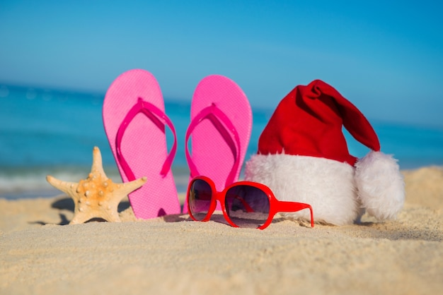 Happy  new year holidays and merry christmas at sea. sandals, sunglasses and santa hat on sandy beach.