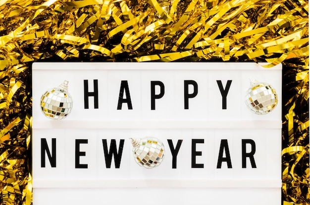 Happy new year inscription on board with baubles