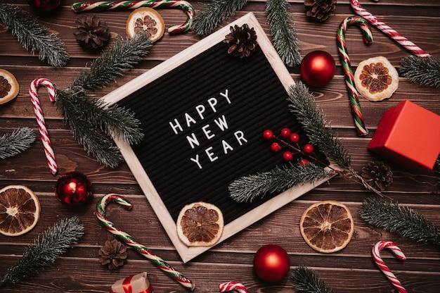 С новым годом надпись на доске в новогодних украшениях, еловых ветках, шишках, шарах, карамельных тростниках. вид сверху. рождественская открытка.