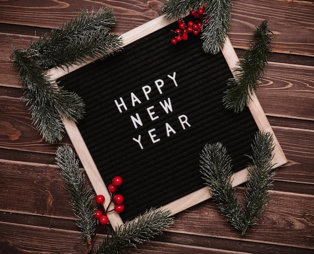 С новым годом надпись на доске для писем в новогодних украшениях еловых веток. вид сверху. рождественская открытка.