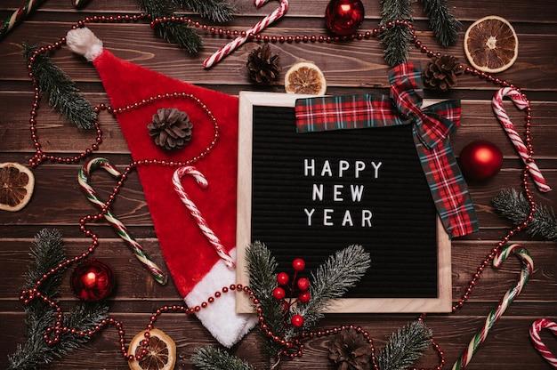 С новым годом надпись на доске в новогодних украшениях, шляпе санты, еловых ветках, шишках, шарах, карамельных тростниках. вид сверху. рождественская открытка.