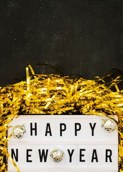Happy new year inscription on white board with baubles