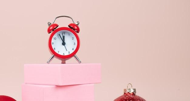 明けましておめでとうございます:ピンクのギフトボックスの真夜中の時計。コピースペースのあるパステル背景。高品質の写真