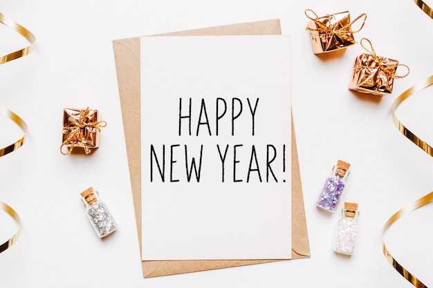 Happy new year note with envelope, gifts and gold glitter stars on white background. merry christmas and new year concept